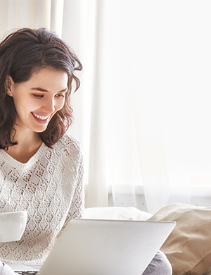 WOMAN LOOKING AT EBANK DRINKING COFFEE