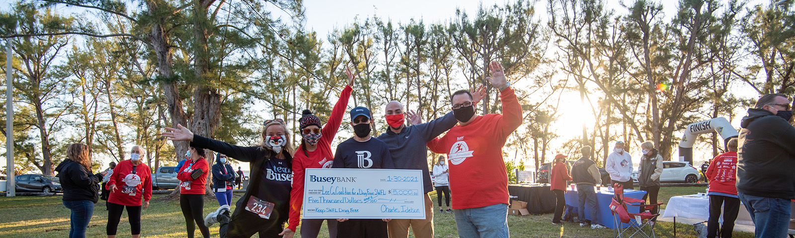Busey Associates with a donation check