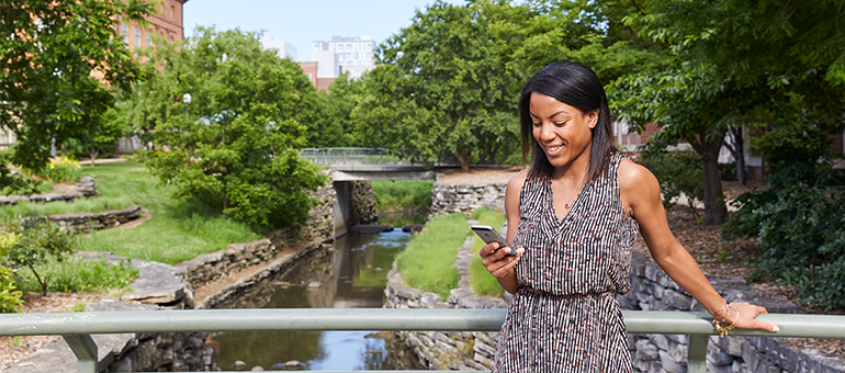 Woman looking at her phone standing on a bridge