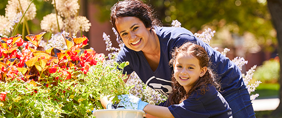 woman and child smiling while gardening